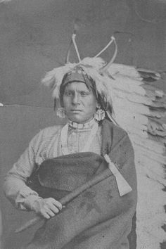 A studio portrait of Kansa Chief Quyulange, also known as Eagle Plume, Eagle Headdress and Eagle Bonnet. He is photographed holding a tomahawk and wearing a headdress.