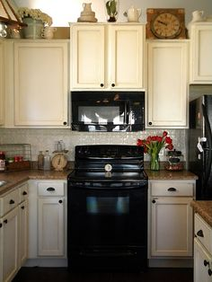 """Behr Swiss Coffee paint with """"Provincial"""" stain wiped on top.  Tin backsplash painted to match.  Same knobs as me..."""