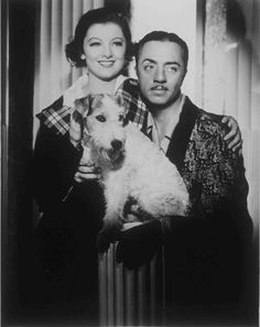 Medium publicity shot of Myrna Loy as Nora and William Powell as Nick holding dog Asta.