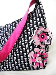 The Roxie Bag is the newest bag in the Brooke Van Gory line. A hobo style slouch bag, this bag is roomy enough for an entire day of shopping, and chic enough for a night on the town! With accents of bright handmade flowers sewn on the outer, this bag is sure to turn heads wherever you go!      This listing is for a CUSTOM Roxie Bag. This means that YOU get to pick the cotton print of the bag, and the strap and lining color. This bag closes with a magnetic snap closure, and has an inset…