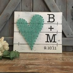 Have initials and a special date painted on this whimsical strung heart artwork to commemorate a special day! The heart makes a perfect gift for a special couple or person or a special message of love in any room in your home! The initials, a plus symbol, and date are hand painted onto a wood slat canvas which is painted and distressed using our unique techniques! Then a heart is nailed onto the canvas and strung with your choice of string color. The finished piece measures approximately 12…