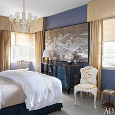 The master bedroom's curtains are made of a Schumacher silk, and the golden lamp and raffia-embroidered chair are by Liz O'Brien Editions | archdigest.com