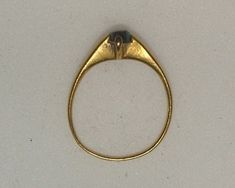 Italy 13th/14th century Gold stirrup ring, the high, flat bezel with two projecting claws set with a rough cabochon sapphire.