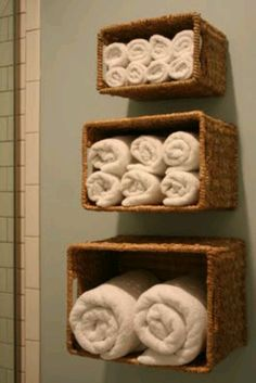 Organize the towels by hanging baskets on the wall in the bathroom.