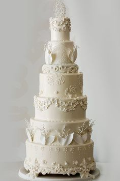 All white wedding cake by Confectionery Designs. Check out more fabulous cake designs in this cake vendor collection.