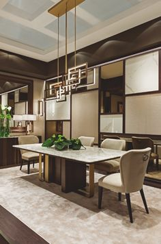 """The """"Symphony in Beige"""" dining room by Oasis features a big table, Saint-Germain, with marble top and a sculpture-like base, by bronze and Bolivar wood; Frances dining velvet chairs and Godot cupboards. The light is provided with a big Edge suspension lamp."""