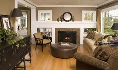 Light wood floors with expresso furniture. Love the mantel and bookshelves combined...high windows above.