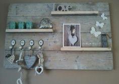Perfect voor aan de muur: Een wand van steigerhout met wandplanken, gevuld met kleine spulletjes.