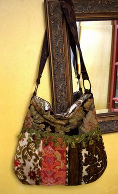 Vintage cut velvet in orange, green, floral and black tapestry. Green tassel accents. Handle with brass rings. Bucket bag style. Inside floral