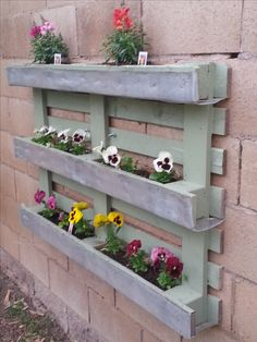 Create a decorative flower box with a pallet, and staple window screen to the pallet to create a pocket that holds the soil to put plant the flowers in. Then bolt the pallet flower box to the cinder block wall to decorate a plain old cinder block wall with beautiful flowers!