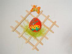 Plaster egg glued on coffee sticks rack