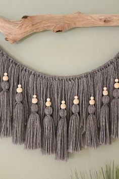 Overview: This driftwood hanging can add texture to any empty wall or hang above a headboard in a bedroom. The driftwood foundation was found washed up on the coast of Italy near Viareggio. I individually measured, cut, and tied each tassel from yarn. I added small wooden beads on top