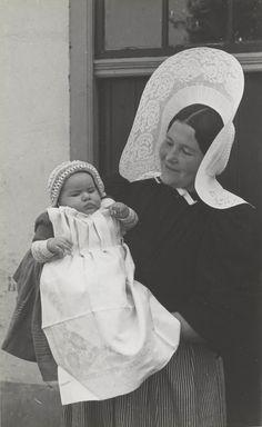 Moeder met baby in Huizer dracht De moeder is gekleed in hedendaagse dracht (anno 1945). De baby is gekleed in een reconstructie van de oudere doopdracht (circa 1920). Het draagt een doopmutsje en een lichtblauw doopjurkje met daarover een geplooid servet. #NoordHolland #Huizen #isabee