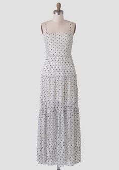 Designed with allover lace, this cream-colored maxi dress features a black polka dot print and a tiered silhouette with ruffled, raw-edge details.