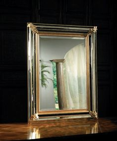 Rectangular mirror with multi- faceted bordered frame in antique gold finish.