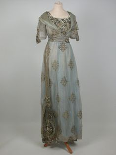 1910 Silk silver gauze gown with woven pattern in gold. Straight style with high waist. Short sleeves with tie effect, inlet panels of gold net. Stomacher panel of gold net sewn with glass beads silver cord, artificial pearls and pastes. Epaulettes of fine crepe cross over effect on front bodice with paste metal buckle. Fastens at back; fastenings are partly concealed by panel of gold net as front.