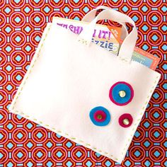 Simple Tote    Perfect for trips to the library or packing a towel for the pool, this tote can be made in four simple steps.  What You Need   -- 4 sheets of white felt   -- 1 sheet of pink and blue felt    -- Needle and embroidery thread     -- Buttons     -- Felt glue