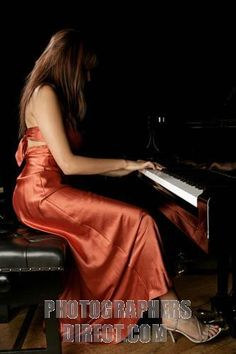 Female pianist in a concert dress playing a grand piano stock photo