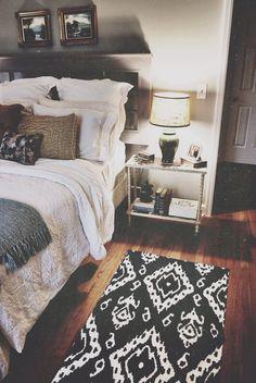 tapete geométrico preto e branco lindo sobre o piso de madeira escura em quarto de decoração escadinava com criado mudo vazado e prateleira de apoio para quadrinhos.