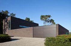 """Gezinswoning in Berlare: Dit ontwerp is eigenlijk een soort project """"op maat"""". De familie die er woont, kan op een discrete en rustige manier leven. Het massieve volume van de woning en de lange muur, waarachter zich de tuin bevindt, geven aan dit familiale toevluchtsoord een gevoel van bescherming."""