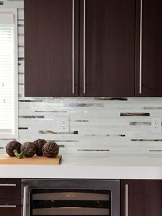"""Light and Shadow In the same kitchen, Caesarstone """"Blizzard"""" for the countertops a glass mosaic backsplash from Mixed-Up Mosaics that combines milky white and eggplant colors with a mirrored tile. """"Keeping the cabinets with a dark finish."""