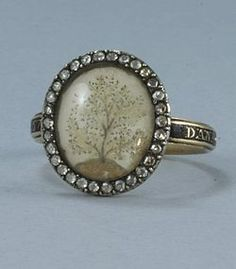 "Georgian mourning ring inscribed ""Dan Gass Ob 28 July 1773 AE 57"".  Macerated hair set on ivory creates this vignette of the symbolic tree of life , barren of colour against a clear sky.  The ring is set with rose cut diamonds.  Of English origin."