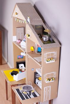 Cardboard Dollhouse DIY with rooftop garden. Look at all the photos, backward and forward to see how clever she was with her use of everyday items to furnish and decorate. Love the tea strainer barbecue and plastic glass chairs. SO clever!