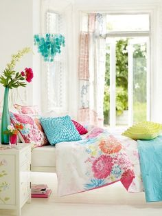 Summery floral bedding in turquoise, fuchsia  and soft white in a white room. Clean and pretty