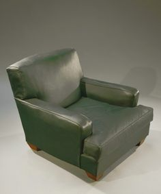 JEAN-MICHEL FRANK (1895-1941) & CHANAUX & CIE   Large low armchair entirely covered with a green leather with straight back and full armrests, resting on four cubic feet sheathed in oak wrecked. Around 1930.   H: 75 cm   W: 84 cm W: 100 cm (restored and reinforced feet)
