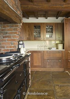 Traditional farmhouse kitchen with flagstone floor, timber beams and range cooker in brick chimney