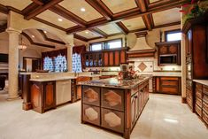 high-end-kitchen-with-pillars-dual-islands-azurite-granite-counters-box-ceiling-and-marble-tile-floors