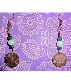 This elegant pair of earrings were handcrafted from modern Uncirculated Thai 25 Satang coins featuring freshwater pearls and emerald  http://www.thesoulshoppe.com/earrings/2602-thailand-uncirculated-25-satang-with-pearls-and-emerald.html