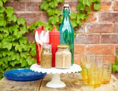 TABLE CADDY  Corral dining must-haves on a cake stand, tucking utensils into mugs and setting condiments on napkins to catch drips. For easy access from every seat, put it on a lazy Susan. Get more ideas for lazy Susans>>