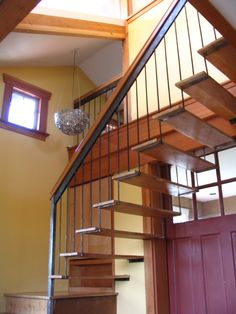 Wooden stairs suspended by metal handrail