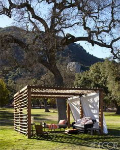 On Portia de Rossi and Ellen DeGeneres's California ranch, a pergola under an oak tree shades a French military day-bed and a wicker sofa.  Tour the entire home.   - ELLEDecor.com