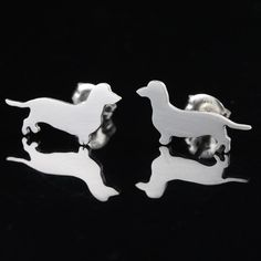 Show your love for yourWiener dog by wearing these cute dachshund earring studs. Each silhouette was hand sawed out of a sterling silver sheet using a jewelers saw with a tiny saw blade. Multi notched ear posts, provide maximum hold, were then fused to each silhouette then earrings were polished. Ear posts and butterfly ear nuts/backs are sterling silver. Wear your fur-baby close to you everyday and everywhere. Measurement:Depth (thickness, including ear post) = 0.46 inchesW...
