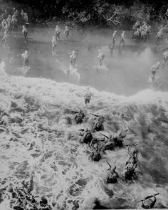 """""""Marines hit three feet of rough water as they leave their LST to take the beach at Cape Gloucester, New Britain."""" Sgt. Robert M. Howard, December 26, 1943."""