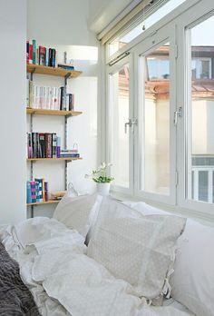 Bookshelves and bed near windows