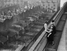 A woman and her two daughters view the surrounding terraced housing from the roof of Hillcott House, a new block of council flats, in Shoreditch, London. (Getty Images) Circa 1938