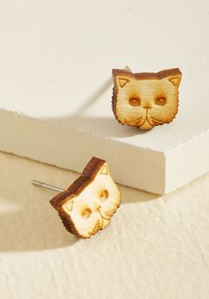 These cat-shaped earrings are bound to elicit emotions aplenty, from inspiration to jubilation! Hand-crafted from birch wood and mounted atop surgical steel posts, these American-made studs are a 'tell-tail' sign that your quirky style goes beyond nine lives - it's simply timeless.