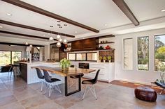 The open layout of this appealing kitchen connects to the rest of the home and to the beautiful outdoor surroundings. An abundance of light and air is grounded by natural textures, creating an engaging design for family life and entertaining.