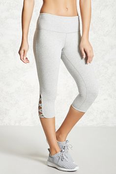A pair of active knit leggings featuring a capri design, side cutouts, and a hidden key pocket.