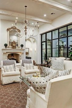 Luxurious white French country living room with black steel windows and French fireplace. #frenchcountry #livingroom #interiordesign #luxuryhome