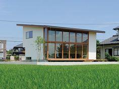 ご主人の自慢のひとつである外観は、片流れ屋根によるシンプルなフォルムと大きく張り出した軒の出が個性的。道路側はプライバシーを考慮し窓の少ないシャープなデザインに、そして田園側は壁一面にガラスを使った大胆な設計となっている。「前から見ても後ろから見てもオッケーなんです! 」とご主人は満足そうに笑う。