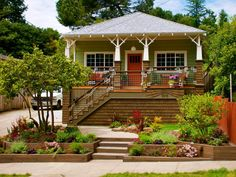 Exterior of a cottage home with front porch and decorative tapered columns. A front porch overlooks a beautiful terraced garden below accessible by a railed staircase.