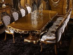 """This exquisite Empire style dining table is 118"""" long and features a double pedestal base. It is adorned with gilded leaf and scroll details. Coordinating display case, breakfront and mirror are also available. None"""
