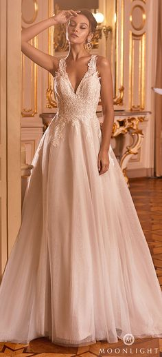 Ball gown wedding dress with halter neckline and lace bodice and tulle skirt | A-line bridal gown with v-neckline | Gilded X Moonlight Collection Fall 2021 Wedding Dresses - J6825 - Belle The Magazine | See more gorgeous bridal gowns by clicking on the photo