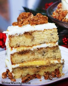 Bananas Foster Cake – all the luscious flavors of Bananas Foster  thanks to a brown sugar rum glaze on each layer.. layers of bananas, a silky cream cheese frosting, and topped off with pieces of sweet, nutty, Southern pecan pralines!