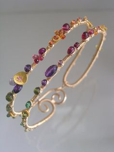 .....color finesse............  Made to order with an up to three week turnaround. Gemstone placement and layout may vary slightly...this way each one remains unique.  14 gauge 14k gold filled wire has been transformed into a wide double layer bangle style bracelet. Adorned with gemstones that include yellow, orange, padparadscha, red sapphires, pink tourmaline, ruby, amethyst, vesuvianite, tsavorite, peridot, green tourmaline and deep blue tourmaline.  Tiny vermeil bead elements and a…