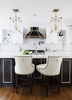 White and black kitchen with two comfortable chairs at island and gold details